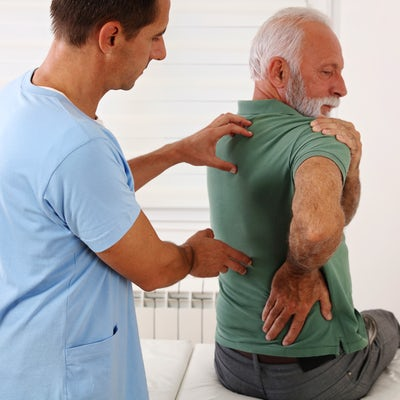 Senior man with back pain. Spine physical therapis
