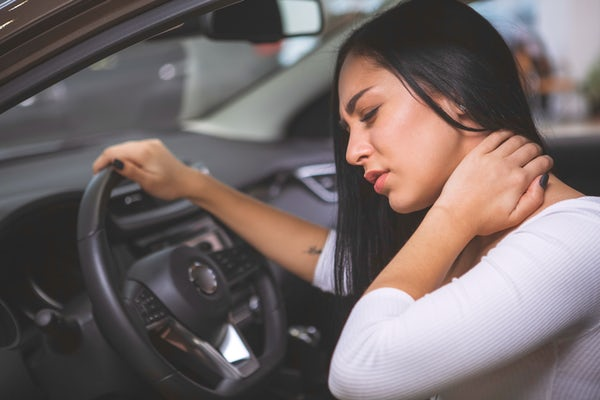Female driver rubbing her aching neck after long d