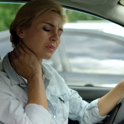Tired female driver sitting in auto and massaging