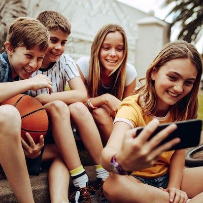 Kids taking a selfie sitting outdoors