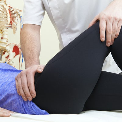 Male Osteopath Treating Female Patient With Hip Pr