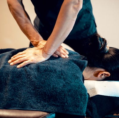 Mid adult male chiropractor treating a female pati