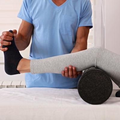 Therapist treating knee of athlete female patient