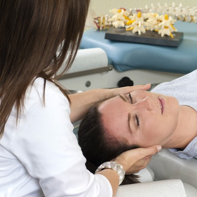 Woman lying on table while chiropractor massages n