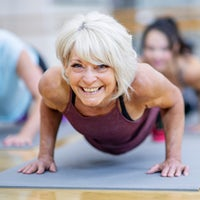Senior Woman in Fitness Class in a Plank Pose Smil