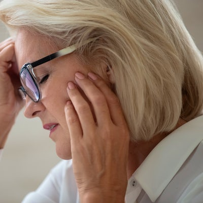 Stressed aged woman in glasses suffering from head