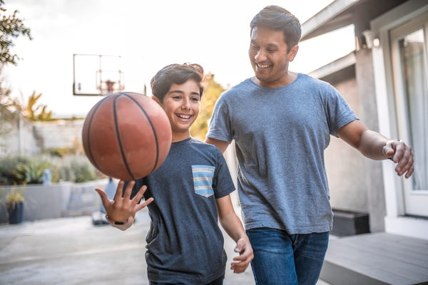 Boy spinning basketball while walking by father