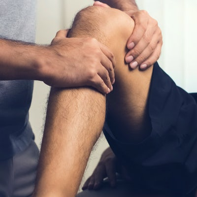 Therapist treating injured knee of athlete male pa