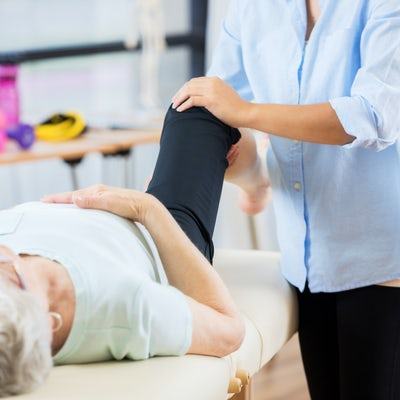 Unrecognizable chiropractor works on senior womans
