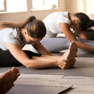 Group of women practicing yoga lesson in paschimot