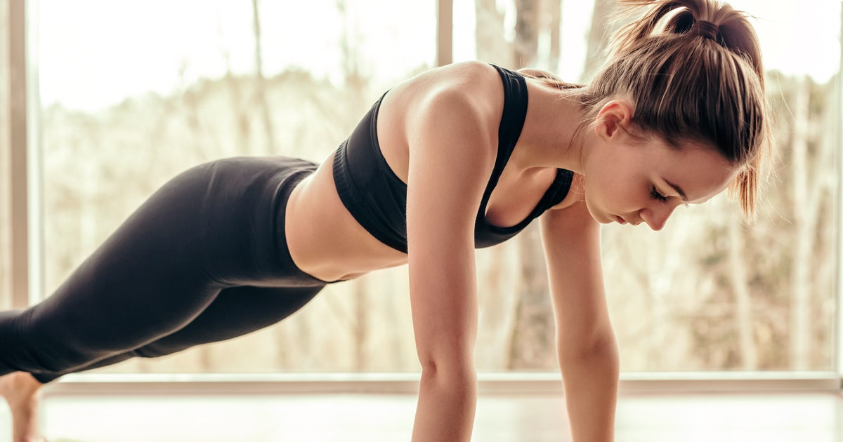 Slim woman doing plank exercise in gym