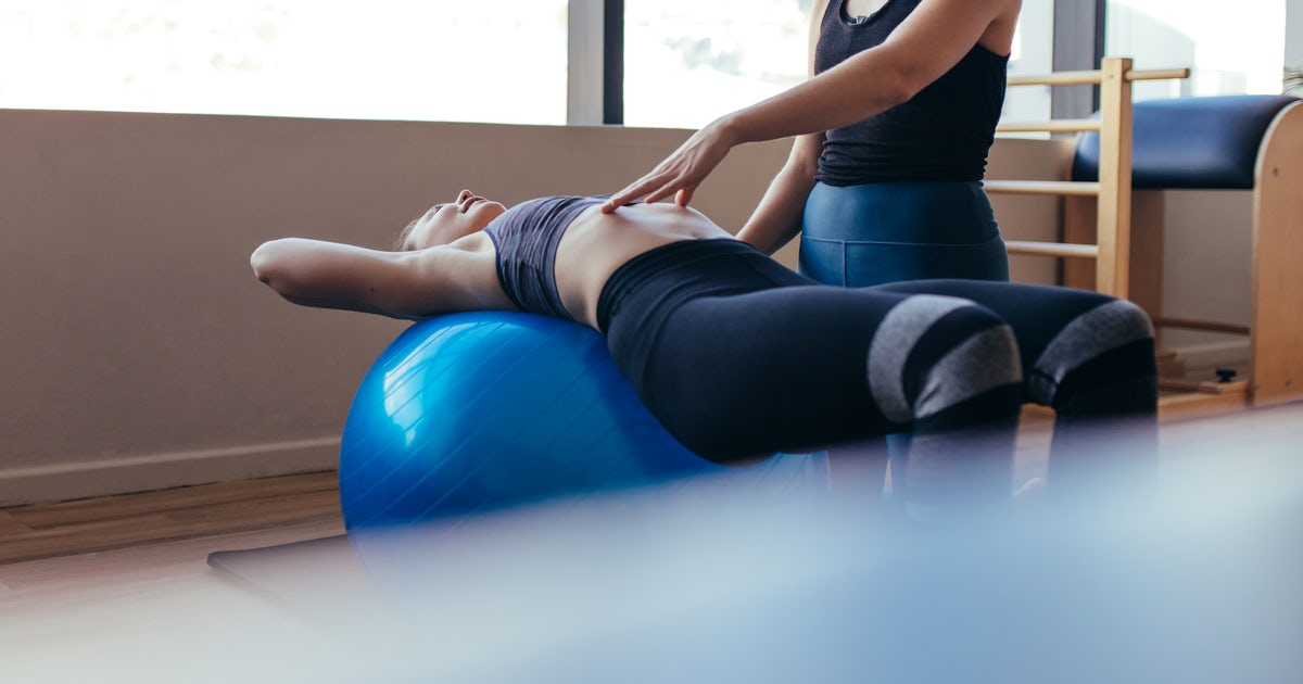 Woman training on exercise ball in a pilates train