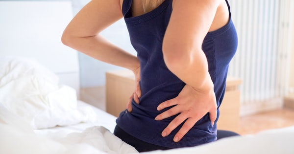 Painful woman awakening and feeling back pain