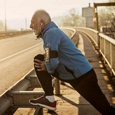 Senior man warming up for jogging on a city bridge