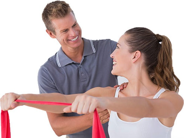 Smiling male chiropractor treating female patient during shoulder rehabilitation
