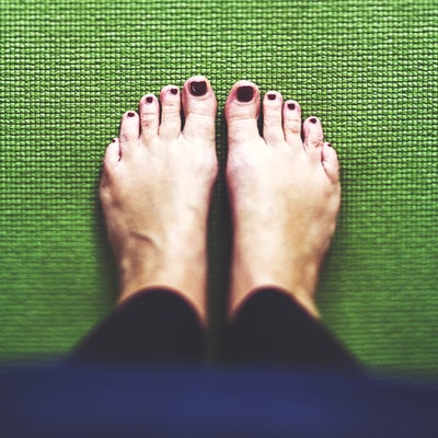 Bare feet on the green Yoga mat