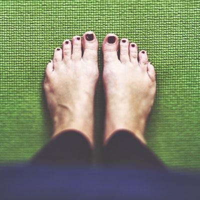 Bare feet on the green Yoga mat
