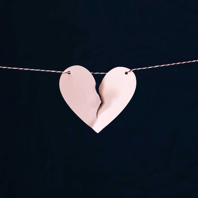A paper heart on a string is nearly torn down the middle