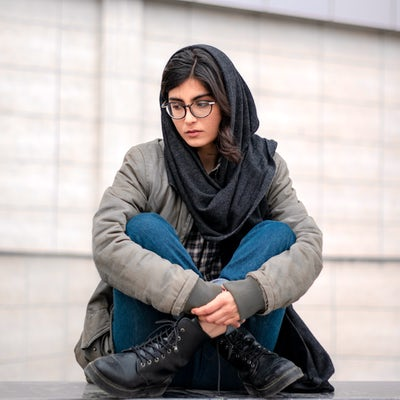 Young woman sitting on ground looks sad