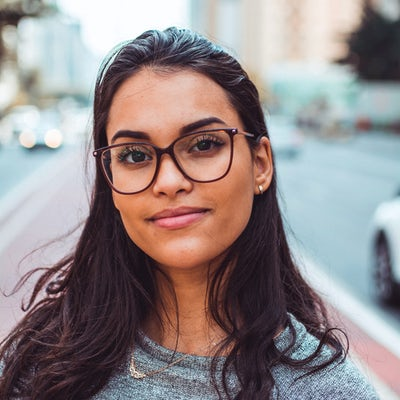 A young woman with glasses smiles